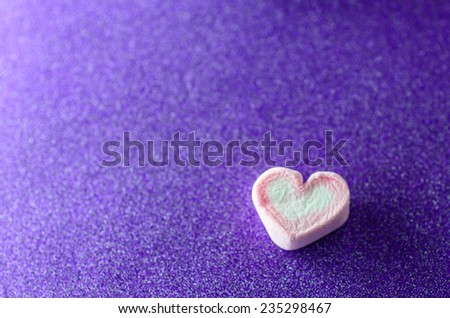 Heart shape mashmellow with purple background. - stock photo