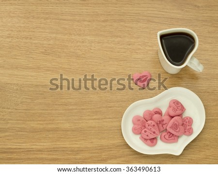 Heart shape of cup with coffee and heart shape of plate with pink sweet hearts in white plate. Love coffee. Top view. Happy Valentines Day background. - stock photo