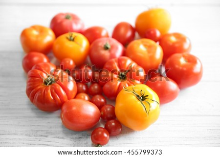 Heart shape of different tomatoes on light wooden background - stock photo