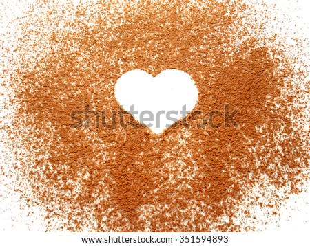 Heart shape on spreading cocoa powder on white background - stock photo