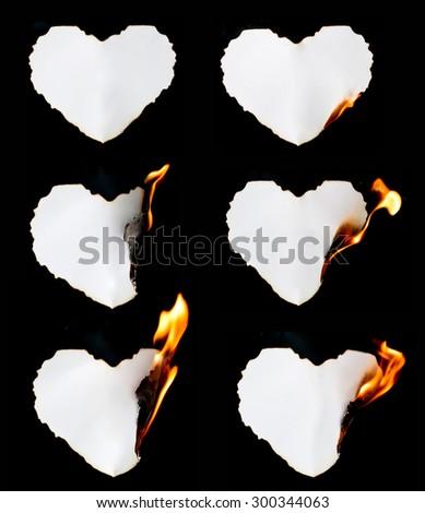 heart shape paper burning on black background - stock photo