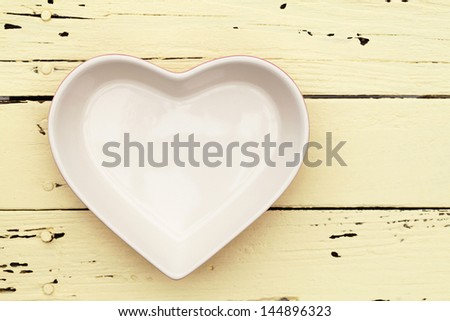 heart shape plate on wooden table? - stock photo