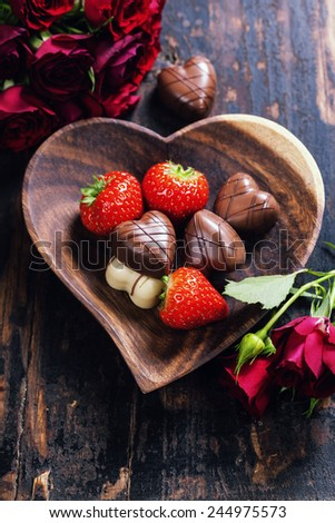 heart shape plate with strawberries and chocolate on wooden table - Valentine's day and love concept - stock photo