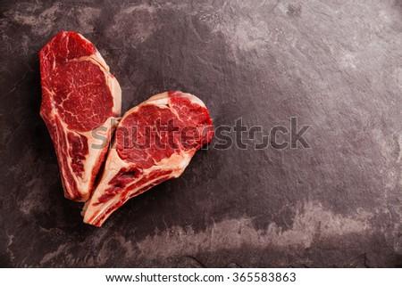 Heart shape Raw fresh meat Ribeye Steak on bone on stone slate background - stock photo