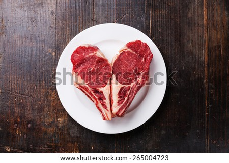 Heart shape Raw meat Ribeye steak entrecote on white plate - stock photo