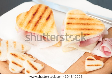 Heart shape toasted sandwiches with ham and cheese - stock photo