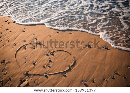 Heart shape written on sand with water in background  - stock photo