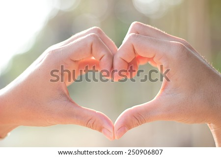 Heart shape, young women hand made heart shape on background blurred. - stock photo