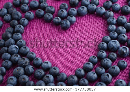 Heart shaped blueberries scattered on a pink jute tablecloth - stock photo