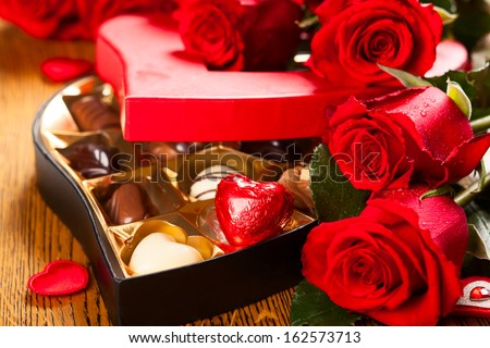 Heart shaped box of chocolate truffles with red roses - stock photo