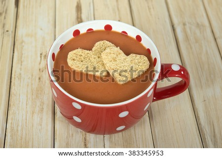 heart shaped bread floating in tomato soup in red and white soup mug on wood - stock photo