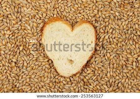 Heart shaped bread surrounded by grains of barley - stock photo