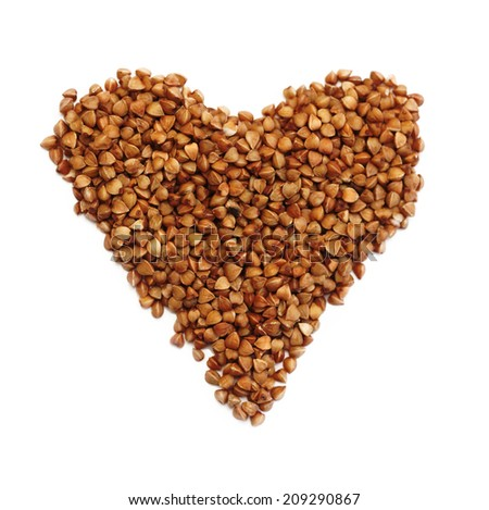 Heart shaped brown buckwheat, valentine heart of brown groats. Isolated on white background  - stock photo