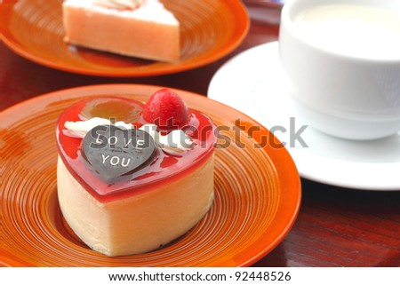 Heart shaped cheese cake with a cup of milk - stock photo