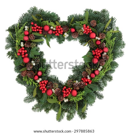 Heart shaped christmas wreath with red bauble decorations, holly, mistletoe, ivy and winter greenery over white background. - stock photo