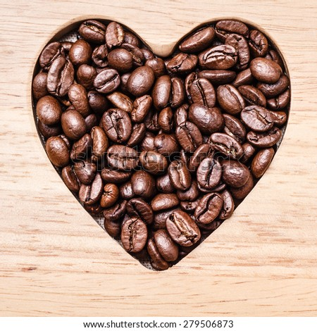 Heart shaped coffee beans on wooden board background. Top view - stock photo