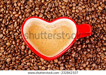 Heart shaped coffee mug dived in coffeen beans, Valentines day. Vertical, with copy space. - stock photo