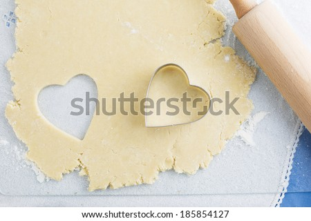 Heart shaped cookie cut out of cookie dough with cutter and rolling pin - stock photo
