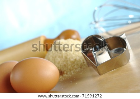 Heart shaped cookie cutter with baking ingredients and utensils such as eggs, brown sugar, rolling pin and a beater (Selective Focus, Focus on the front of the cookie cutter) - stock photo