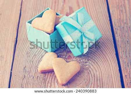 Heart shaped cookies in a blue gift box on a wooden background in a vintage style for Valentine's day. Love, holidays concept. Selective focus - stock photo