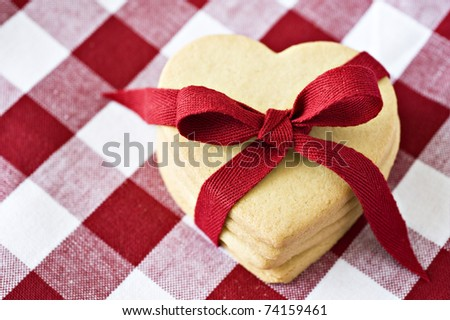 Heart shaped cookies with a red ribbon on cloth - stock photo