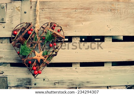 Heart shaped decorative element on a wooden background - stock photo