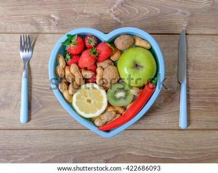 Heart shaped dish with vegetables isolated on wooden background - stock photo