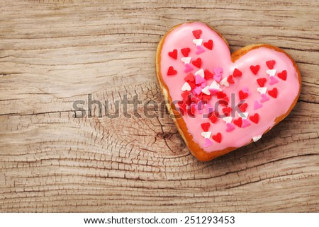 Heart shaped donut on wooden background - stock photo