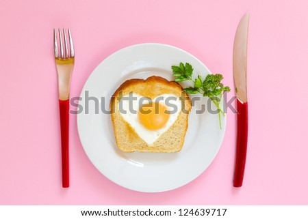 Heart shaped egg in toast on a white plate with a red handled fork and knife.  Valentine's Day concept. Top view looking down. - stock photo