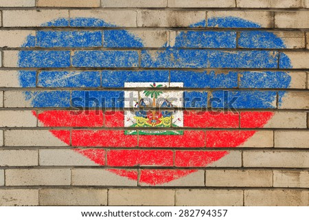 heart shaped flag in colors of Haiti on brick wall - stock photo