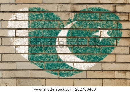heart shaped flag in colors of Pakistan on brick wall - stock photo