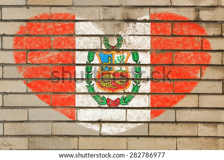 heart shaped flag in colors of peru on brick wall - stock photo