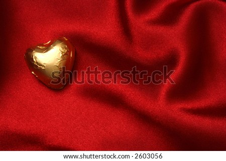 Heart shaped foiled chocolate on red satin - stock photo