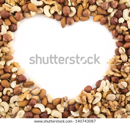 Heart shaped frame made of peanut, hazelnut, walnut, almond, pistachio nut mix - stock photo