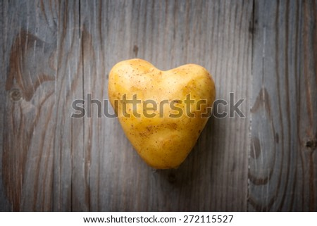 Heart shaped golden potato spud on Wooden Table Background, Concept and Idea of Food Cook Rustic Still life Style. Dramatic light table setting. - stock photo
