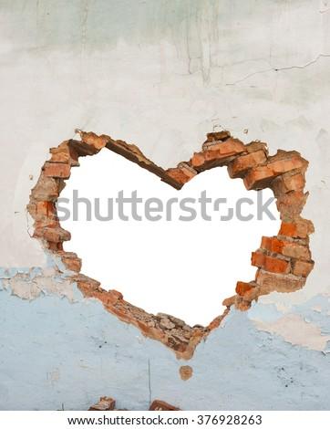 Heart shaped hole in old brick wall - stock photo