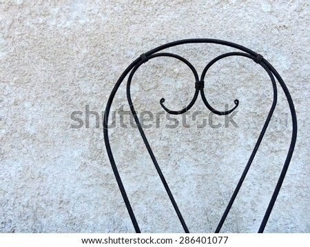 Heart shaped iron chair backrest on a gray concrete wall background. - stock photo