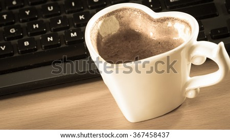 Heart shaped mug cup of coffee next to laptop notebook computer keyboard. Office work desk. - stock photo