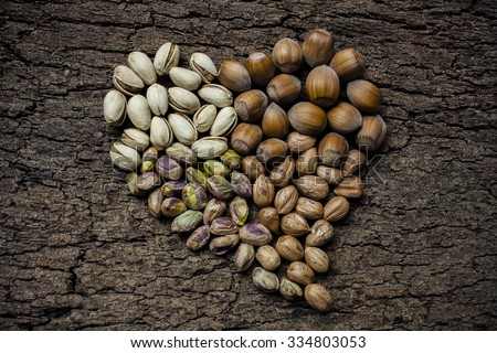 Heart - shaped nuts: hazelnuts, pistachios and cashews - stock photo