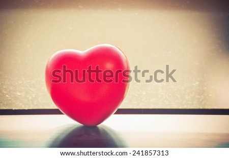 Heart-shaped of red against window with vintage background, feel the atmosphere sad. - stock photo