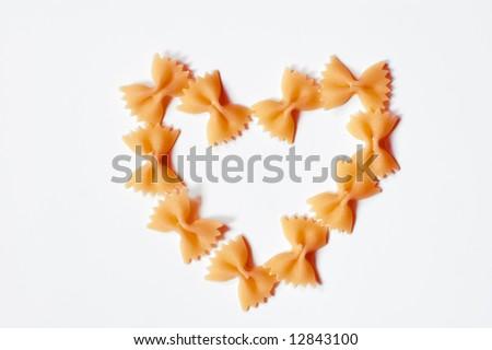 Heart shaped pasta, farfalle on white background - stock photo