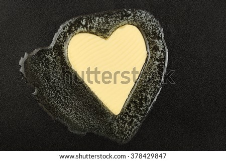 heart-shaped piece of butter melting on black pan - stock photo