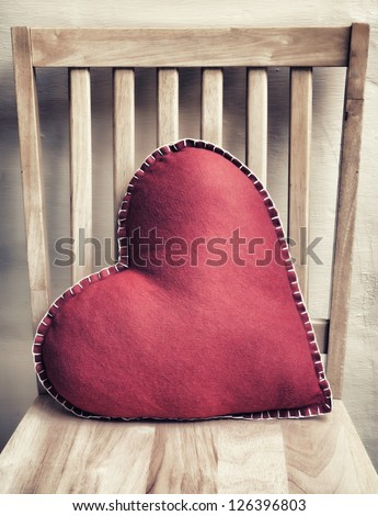 Heart shaped pillow on wooden chair with vintage look - stock photo