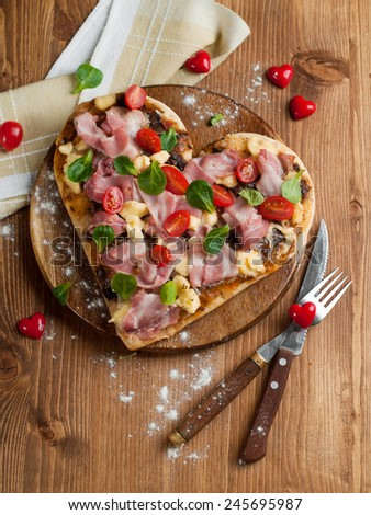Heart shaped pizza with bacon and vegetables, selective focus - stock photo
