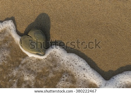 Heart shaped rock washed by the sea on a sandy beach. - stock photo