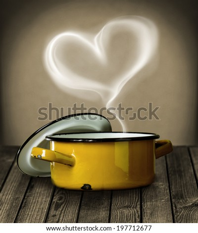 Heart shaped steam hovering in the air above a yellow enameled metal cooking pot symbolic of love on a rustic wooden kitchen counter - stock photo