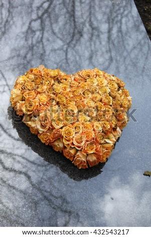 Heart shaped sympathy flowers on a gravestone - stock photo