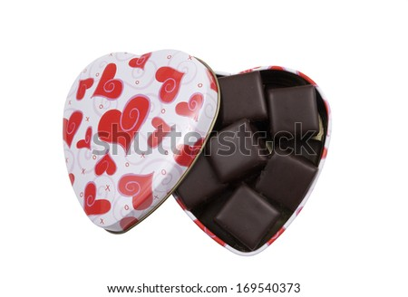 heart shaped tin box filled with chocolate covered cake squares on a white background - stock photo