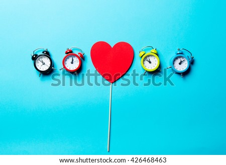 heart shaped toy and colorful clocks on the blue background - stock photo