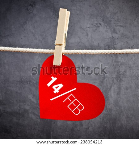 Heart shaped Valentine's Day card with date February 14th attached to a rope with clothes pins. Romance, love and affection concept. - stock photo